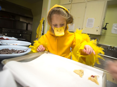 JIM VAIKNORAS/Staff photo Allison Lavallee, 5, who is dressed as a duck, helps make hamantaschen, a Jewish cookie, at a Purim Celebration at the Congregation Ahavas Achim in Newburyport Sunday morning. The celebration included games and prizes, crafts, face painting and a costume contest.