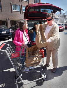BRYAN EATON/Staff photo. Roseann Robillard, Director of the Newburyport Council on Aging, center, worked with Mary Kelly, Activities Director, out of view, to deliver food from Our Neighbor's Table to several senior residents in the community, here to Helen Dove and others at the Sullivan Building. The Thursday food bank which operates out of Community Service on Summer Street has changed the usual operating procedures, due to the Corona virus. As long residents are unable to visit Community Service to obtain food and other necessities, the Council on Aging will assist with placing orders and making deliveries.  Roseann and Mary are available at the Senior/Community Center for more information 978-462-0430.