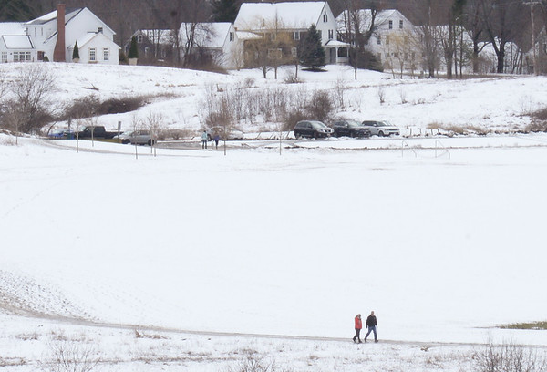 BRYAN EATON/Staff photo. Two walkers travel along a trail at Woodsom Farm in Amesbury on Tuesday afternoon where people and their dogs usually go. The further from the ocean, the more snow fell, though nobody was seen sledding on the hill nearby.
