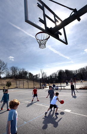BRYAN EATON/Staff Photo. First-graders at the Bresnahan School in Newburyport play some basketball at recess under a bright sun with the temperature at 60 degrees on Tuesday afternoon.