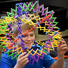 BRYAN EATON/Staff Photo. Jack Parr, 11, and friends took turns putting there heads into an Hoberman sphere, an isokinetic structure that resembles a geodesic dome, but is capable of folding down to a fraction of its normal size by the scissor-like action of its joints. They were in the games room at the Newburyport Rec Center were others were playing chess and doing puzzles.