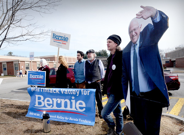 BRYAN EATON/Staff Photo. Eric Peirce, right, stands next to a cutout of Senator Bernie Sanders as he and others campaign outside Amesbury High School. From left, Maryanne Snow, Leslie, Matt Burton and John Proctor.