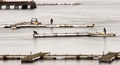 BRYAN EATON/Staff photo. With the first full day of spring on Friday hitting 60 degrees there was  work going on in area boatyards and marinas. Here workers from the Ring's Island Marina in Salisbury set up docks for the season in a view from the Gillis Bridge.