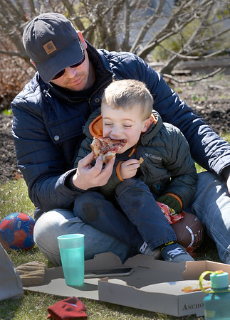 BRYAN EATON/Staff photo. Henry Wilkinson, 4, of Newbury bites into some Anchor Pizza takeout his dad Don picked up to enjoy at Newburyport's Waterfront Park on the better half of the weekend. After, they joined his mom, Alex, and brother Miles, 18 months, who were checking out the fishing boats tied up at the embayment along the boardwalk.