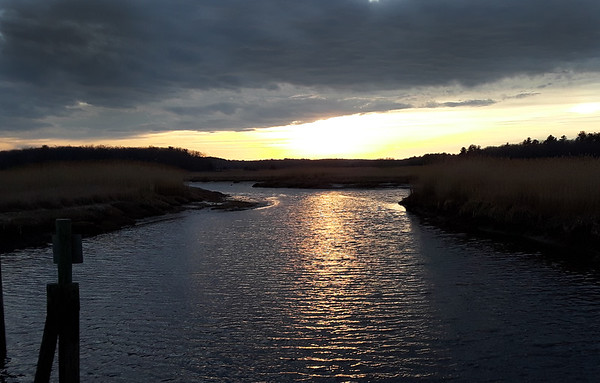 BRYAN EATON/Staff photo. The setting sun peeks below a bank of clouds reflecting onto Town Creek along the Great Eastern Marsh Trail in Salisbury over the weekend.