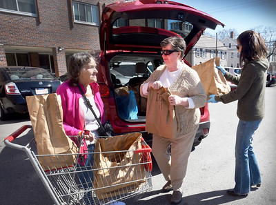 BRYAN EATON/Staff photo. Roseann Robillard, Director of the Newburyport Council on Aging, center, worked with Mary Kelly, Activities Director, right, to deliver food from Our Neighbor's Table to several senior residents in the community, here to Helen Dove and others at the Sullivan Building. The Thursday food bank which operates out of Community Service on Summer Street has changed the usual operating procedures, due to the Corona virus. As long residents are unable to visit Community Service to obtain food and other necessities, the Council on Aging will assist with placing orders and making deliveries.  Roseann and Mary are available at the Senior/Community Center for more information 978-462-0430.