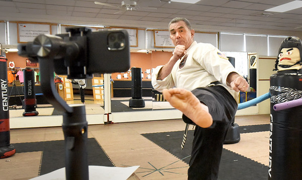BRYAN EATON/Staff photo. Karate instructor Kendall Buhl watched a recording of a student's workout from their home at his Salisbury martial arts studio. He here gives some tips on the workout taped on his cellphone to send the student.