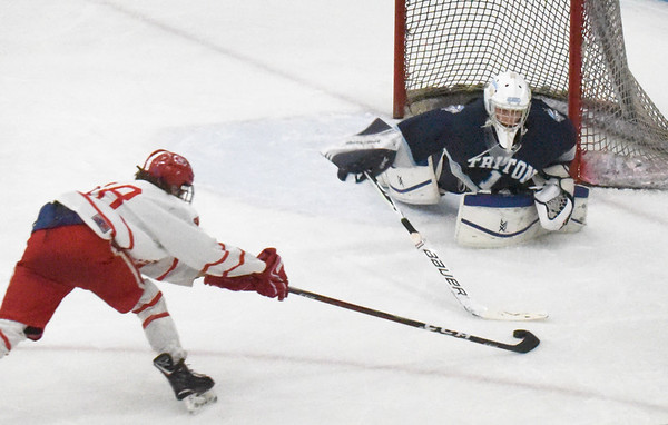 BRYAN EATON/Staff photo. Masconomet's Logan Campbell shoots on Triton goalie Wesley Rollins who makes the save.