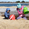 BRYAN EATON/Staff photo. Everett Campano, 2, of Amesbury, left, and his sister Hazel, 6, get out of the wind behind a huge piece of driftwood and they fill their sand pails. They wanted to get out of the house so their mother, Amanda, took them to Plum Island Point on Tuesday morning, bundled from the cold though the temperature rose through the afternoon.