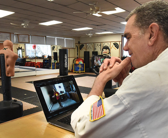 BRYAN EATON/Staff photo. The Dojo karate instructor Kendall Buhl watches a recording of a student's workout from their home at his Salisbury martial arts studio. He then records his thoughts on the workout and gives some pointers for improvement.