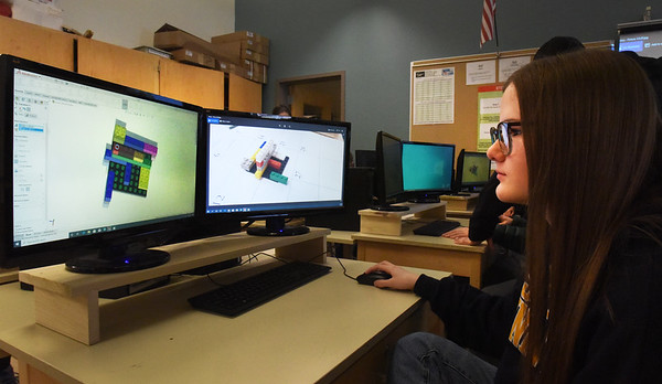 BRYAN EATON/Staff photo. Mia Ziomek, 17, and classmate constructs 3-D Legos in the engineering lab at Amesbury High School on computers that were donated by an alum.