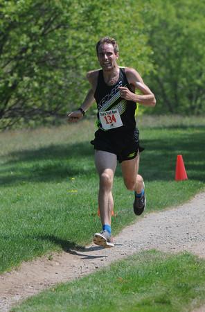 JIM VAIKNORAS/Staff photo  Winner Nate Jenkins sprints to the finish at Trav's Trail Run at Maudslay State Park in Newburyport.