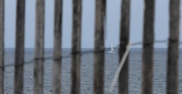 JIM VAIKNORAS/Staff photo A sail boat glides along the horizon as seen through a sea fence on Plum Island.
