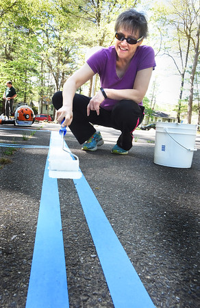 BRYAN EATON/Staff photo. First Religious Society Unitarian Universalist Church members cleaned up, painted and more to fix up Woodman Park for the city of Newburyport on Saturday. Julie Menin painted lines on four square court on one section of the basketball court.