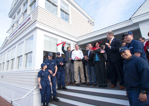 JIM VAIKNORAS/staff photo Members of Coast Guard join from the left Planning & <br />  Senior Project Manager Geordie Vining,  Newburyport Harbormaster Paul Hogg, Harbor Commission Chairman Andrew Casson, Newburyport mayor Donna Holaday, representative James Kelcourse, and many others at a ribbon cutting ceremony opening the new Harbormaster Head Quarters Thursday night.