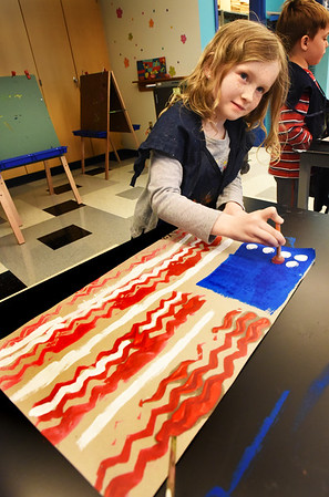 BRYAN EATON/Staff photo. Kaya Maglio, 5, and her kindergarten classmates made American flags in Pam Jamison's art class at the Bresnahan School in Newburyport. The flags will be part of the school's Memorial Day Remembrance on Friday.