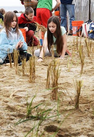 BRYAN EATON/Staff photo. Kayla Harrington, left, and Devin Jackson, both 10, put in dune grass.