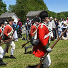 BRYAN EATON/Staff photo. The Redcoats head onto the battle field past onlookers.