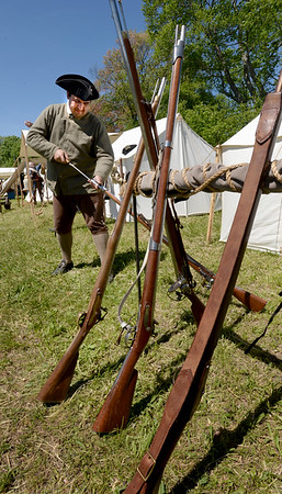 BRYAN EATON/Staff photo. Laurent Dubois of Littleton, originally from France, cleans the muskets.