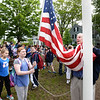 BRYAN EATON/Staff photo. Amesbury Elementary School's annual Memorial Day flag community service field trip took place on Wednesday with stops at the Polish American War Memorial, here, and later planting flags on the graves of soldiers and sailors at Mt. Prospect Cemetery. Veteran's agent Kevin Hunt put up new American, state of Massachusetts and MIA/POW flags with each student taking a turn to pull the flags up in increments.