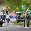 BRYAN EATON/Staff photo. Supporters hold signs for their candidates outside Newbury Town Hall on Tuesday afternoon. Rowley went to the polls for the renovation and addition to the Pine Grove School.