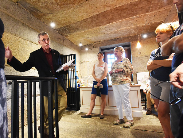 BRYAN EATON/Staff photo. Newburyport Preservation Trust board member Reg Bacon speaks to visitors at the old Newburyport Jail (Gaol) on Friday night. The open house at the privately-owned building was a fundraiser for the trust.