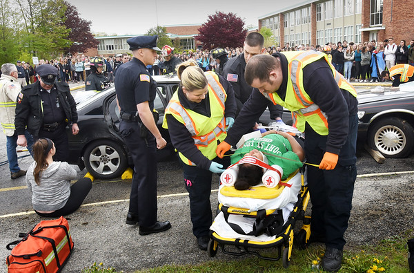 BRYAN EATON/Staff photo. Rescue personnel stabilize a passenger in a mock drunken driving crash at Pentucket High School on Monday afternoon. Area safety agencies, along with the school's Safety and Public Safety Academy coordinated the effort to educate students about drinking and driving as prom and graduation season is here.