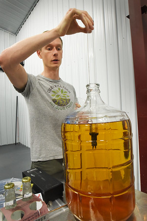 BRYAN EATON/Staff photo. Cook draws a sample from a carboy for testing.