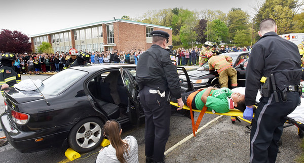 BRYAN EATON/Staff photo. Rescue personnel extricate a passenger in a mock drunken driving crash at Pentucket High School on Monday afternoon. Area safety agencies, along with the school's Safety and Public Safety Academy coordinated the effort to educate students about drinking and driving as prom and graduation season is here.