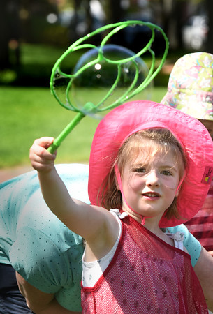 BRYAN EATON/Staff photo. Fiona Hickey, 5, uses a giant wand to create bubbles at Newburyport's Waterfront Park. The younger children at the Newburyport Montessori School usually have Bubble Day on the last week of school, but since it was so warm on Thursday, they held it then.