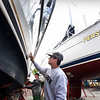BRYAN EATON/Staff photo. Despite the unseasonably cold, windy and rainy weather, there is activity on the Newburyport Waterfront. AJ Keating, left, of North Andover and Brett Kochanski of Newburyport spent Friday afternoon waxing and buffing a friend's boat at the Windward Yacht Yard. The 38' motorboat will be returned to the Merrimack River on Tuesday when the temperature is forecast to be more seasonal with the sun appearing.