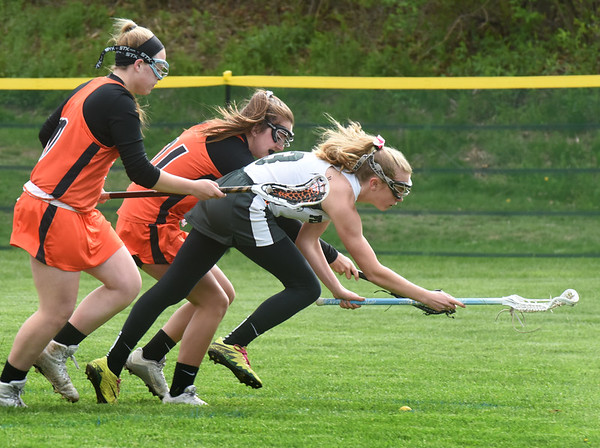 BRYAN EATON/Staff photo. Pentucket's Anna Wyner heads for the grass as she and two Ipswich players go for the ball.