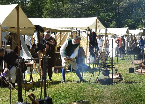 BRYAN EATON/Staff photo. The American revolutionary reenactors tend to their cooking fires.