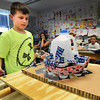 "BRYAN EATON/Staff photo. Students Gale Regis' science class held their ""Great Shake"" on Thursday testing out the seismographs that they designed and built. Caleb Scotch, 12, pictured, and his teammates, Eli Blouin, Matthew Legault and Tyler Wilson, all 12, shake their Hydro Scope using a gallon water jug with holes above each cup. The water is filled just below the holes, and when they roll their seismograph,water spills in certain cups where they can ascertain which direction the shock waves would come from."