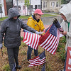JIM VAIKNORAS/staff photo Merrimac Garden Club Members Carolyn Force, Janet Lavoie,and Thelma Gibbs put out flags in the rain puts in flags in the rain in Merrimac Square Friday. Each flag contained the name of a veteran, and was placed for a $10 donation with proceeds going to Veteran's Services.<br /> The flags are reusable and will be placed ever year  before Memorial Day. Also there, not shown are Susan Barbrick and Sandy Venner.