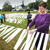 BRYAN EATON/Staff photo. Amesbury artist Ellen Rogers and volunteers space out the strips of material with the names off fallen soldiers from Iraq and Afghanistan at her Remembering Our Fallen art exhibit in the field next to her West Winkley Street home. From left, Maureen Sunner, Sydney Sunner, Ashley Osborns, Rogers, and Roger Deschenes, out of view.