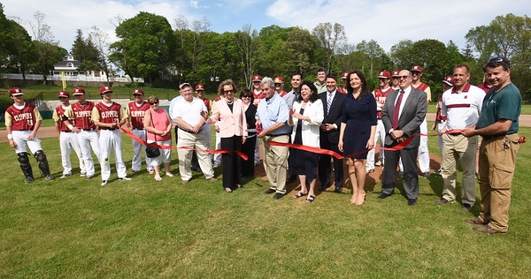 BRYAN EATON/Staff photo. Surrounded by city and school officials and the Newburyport HIgh School baseball team, Richie Eaton cuts the ribbon during the dedication of the baseball field named after the longtime civic volunteer and youth coach.