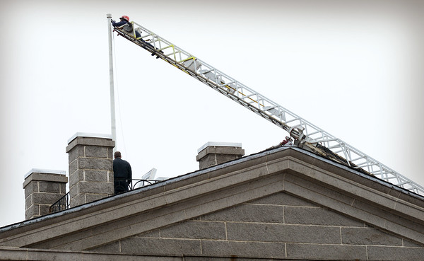 BRYAN EATON/Staff photo. The halyard, or flag line, on the flagpole of the Custom House Maritime Museum had been damaged from the weight of the flag. The Newburyport Fire Department helped out with their ladder truck, the assignment as a drill, to get the pole ready for the arrival of the tall ships.