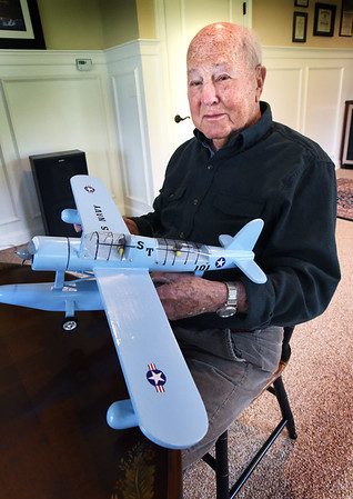 BRYAN EATON/Staff photo. Joseph Babineau holds a model of a Vought OS2U Kingfisher which was an American catapult-launched observation floatplane that he flew in World War II. The West Newbury resident is going to be the grand marshall of the town's Memorial Day Parade on Monday.