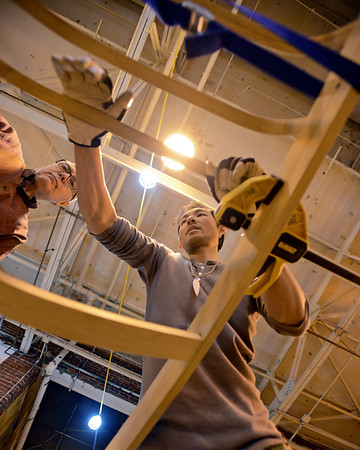 RYAN HUTTON/ Staff photo<br /> Kiliii Yüyan, right, shows Bob Budding, left, how to firmly affix the wooden ribs to his kayak at a kayak building workshop hosted at CI Works in Amesbury.