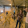 RYAN HUTTON/ Staff photo<br /> Addie Asbridge, left, looks over the progress Rick Brickley, right, is making on his paddle at a kayak building workshop hosted at CI Works in Amesbury.
