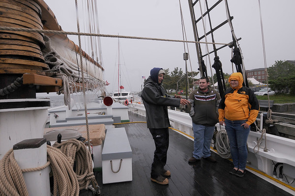 JIM VAIKNORAS/staff photo Crew member John Emmet of Gloucester talks with visitors Zeke Pasquavelli and Leia Sturtevant about the Adventure, one of 2 tall ships docked on Newburyport's waterfront. The ships will be visiting till Monday .
