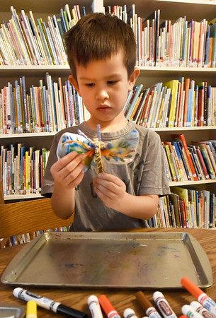 BRYAN EATON/Staff photo. Cameron Snell, 5, creates a tye-dye butterfly at the Emma Andrews Library in Newburyport on Friday after having books about butterflies read to them. Youngsters from Our Secret Garden preschool at the First Newbury Parish took a field trip to the branch library.