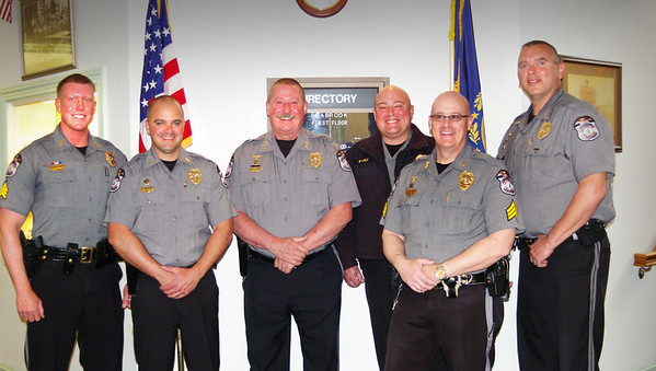 ANGELJEAN CHIARAMIDA/Staff photo. Joining new officers on Monday after their official swearing are police Chief Michael Gallagher and Deputy Chief Brett Walker, center. Newly sworn in officers are, from the left, Sgt. Justin Murphy, Lt. Kevin Gelineau, Gallagher, Walker, Sgt. Patrick Smart and Lt. Jason Allen.