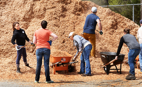 BRYAN EATON/Staff photo. Volunteers from Timberland attack a huge pile of mulch at the Seabrook Recreation Center on Thursday morning. The 65 volunteers were sprucing up the landscaping in area, pulling weeds, raking and spreading the mulch around the playground area.