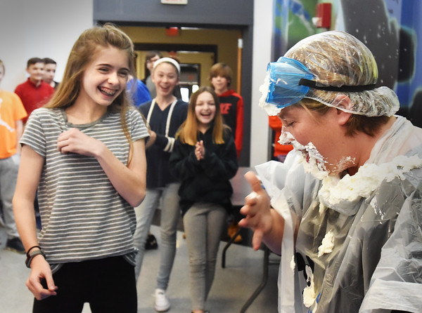 BRYAN EATON/Staff photo. Julia Penny, 13, laughs as teacher Kristen Dore wipes whipped cream off her face after the student lobbed it at her at Amesbury MIddle School on Monday morning. The event was a fundraiser for the school's Destination Imagination team which is going to Tennessee in May for the GLOBAL DI finals. Several teaches volunteered to be hit and students got entered in a raffle with their donations.