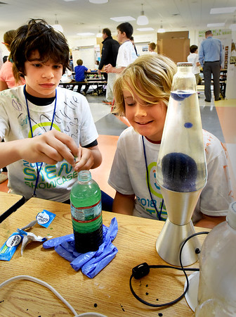 BRYAN EATON/Staff photo. Patrick Skiba, left, and Sam Fountain, both 11, had the hypothosis that a store-bought Lava Lamp, right, would be better than one they could create. Creating one with water, vegetable oil, Alka-Seltzer and food coloring, they felt theirs was better.