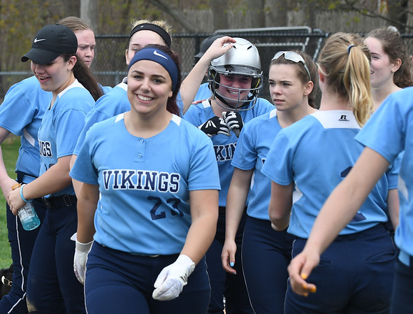 JIM VAIKNORAS/Staff photo Triton players congradulate teammate Eve Pacos, in helmet,  after her home run at Perry Field in Amesbury Friday.