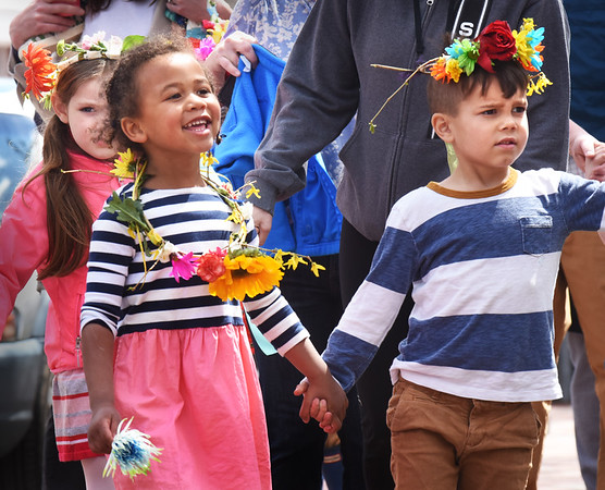BRYAN EATON/Staff photo. June Zeucher, 4, and Corbin Young, 5, along with McKinley Noonan, 5, back, left, march along Pleasant Street in Newburyport from the Newburyport Montessori School to Brown Square. The school was having their annual May Day Celebration where they formed a large circle and sang songs.
