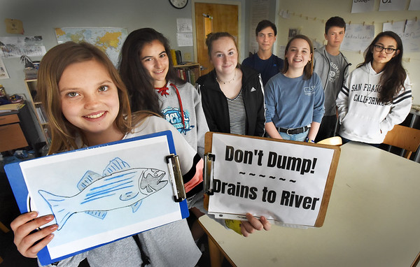 BRYAN EATON/Staff photo. Groups of students at River Valley Charter School have been working on a set of environmentally themed projects, one of which includes labelling and stenciling the city's storm drains to prevent dumping. Working on that project, from left, Emma Crepeau, 13, Izzy Kirby, 14, Katherine O'Connor, 14, Jaden Dussault, 14, Megan Guild, 13, Oliver Looker, 13, and Lucy Jones, 12.